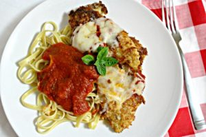 This is an easy Chicken Parmesan recipe that combines bread crumbs and cheese to coat the chicken and is served with jar sauce and long pasta.