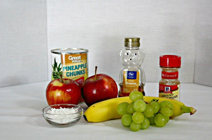 This is a refreshing fruit salad that combines canned pineapple, fresh apples, grapes, coconut, and honey with a dash of cinnamon.