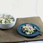 Want a light potato salad recipe? This version combines red potatoes and onions, sweet pickles, celery, plain yogurt, mayo, and a little Dijon mustard.
