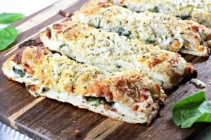 Spinach & Feta Stuffed Pizza Bread: Premade pizza crust filled with Alfredo sauce, spinach, cheeses, and seasoning then baked to perfection!