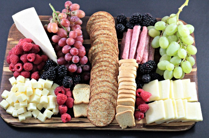 Perfect Party Cheese Board features Stella Cheeses, Genoa Salami, crackers, mini toast, red and green grapes, raspberries and blackberries.