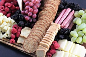 This Perfect Party Cheese Board features Stella Cheeses, Genoa Salami, crackers, mini toast, red and green grapes, raspberries and blackberries.