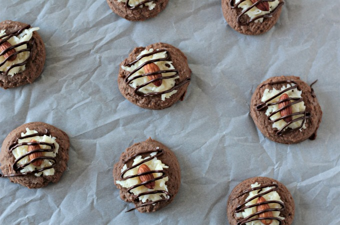 Almond Joy Cookies feature a light and fluffy chocolate cookie baked to perfection, topped with sweet gooey coconut candy then drizzled with chocolate.