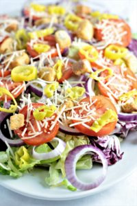 Italian Style Salad: Romaine mix, butter, and baby red lettuces, radicchio, Roma tomatoes, red onion, pepperoncini, Parmesan cheese, and croutons.