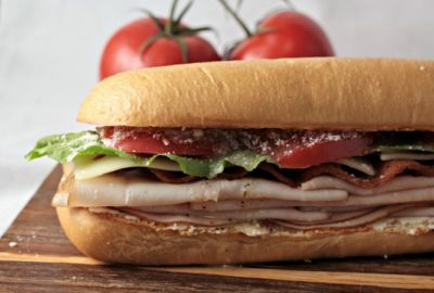Turkey BLT features bacon, lettuce, tomato, Swiss cheese, cream cheese, Parmesan cheese, and Italian dressing on a hoagie bun. Simply the best Turkey BLT!