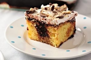 Twix Poke Cake combines boxed yellow cake mix, caramel topping, chocolate pudding, whipped topping and Twix candy bars to make an easy and yummy dessert!