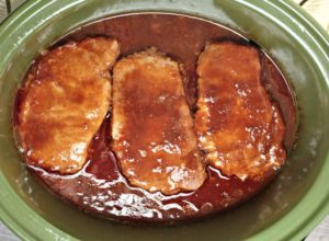 Crockpot BBQ Cola Pork Chops only require a slow cooker and 4 ingredients; pork chops, barbecue sauce, Pepsi or Coke, and ketchup. Easy and delicious!