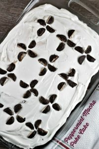 Peppermint Mocha Poke Cake features boxed chocolate cake, International Delight creamer, pudding, whipped topping and peppermint patty candies.