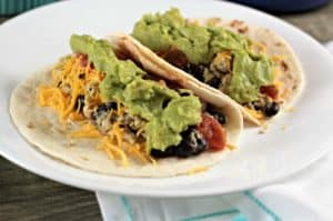Simply Avocado® Breakfast Soft Tacos feature scrambled eggs, black beans, cheese, salsa, and avocado atop a warm flour tortilla, perfect for any meal!